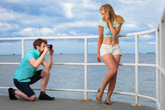 Le jeune couple dans l'amour prend des photos sur la jetée de mer Photos libres de droits