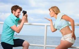 Le jeune couple dans l'amour prend des photos sur la jetée de mer Photographie stock libre de droits