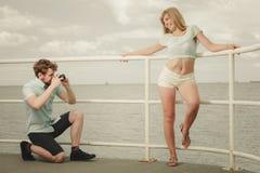 Le jeune couple dans l'amour prend des photos sur la jetée de mer Images stock