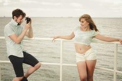 Le jeune couple dans l'amour prend des photos sur la jetée de mer Photos stock