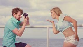 Le jeune couple dans l'amour prend des photos sur la jetée de mer Image stock