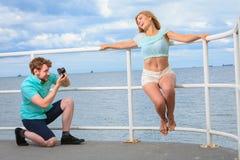 Le jeune couple dans l'amour prend des photos sur la jetée de mer Photo libre de droits