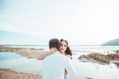Le jeune couple dans l'amour se repose ensemble près du lac et les montagnes, la belle femme caucasienne et l'homme étaient amour Photo libre de droits