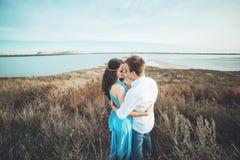 Le jeune couple dans l'amour se repose ensemble près du lac et les montagnes, la belle femme caucasienne et l'homme étaient amour Images libres de droits