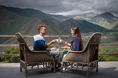 Le jeune couple dans la bonne humeur se repose sur la terrasse avec des tasses de café dans le matin Photographie stock libre de droits