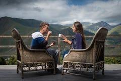 Le jeune couple dans la bonne humeur se repose sur la terrasse avec des tasses de café dans le matin Photos stock