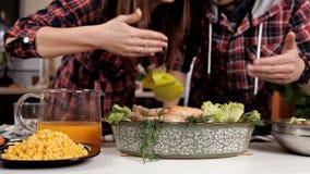 Le jeune couple dans la cuisine, met sur le poulet cuit au four par table pour le dîner clips vidéos