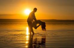 Le jeune couple danse dans l'eau sur la plage d'?t? Coucher du soleil au-dessus de la mer Deux silhouettes contre le soleil Calme images stock