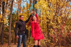 Le jeune couple danse dans la forêt d'automne parmi les arbres colorés Images stock