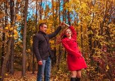 Le jeune couple danse dans la forêt d'automne parmi les arbres colorés Photos libres de droits