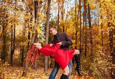 Le jeune couple danse dans la forêt d'automne parmi les arbres colorés Images libres de droits