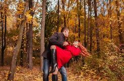 Le jeune couple danse dans la forêt d'automne parmi les arbres colorés Image libre de droits