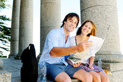 Le jeune couple de déplacement consulte une carte Images libres de droits