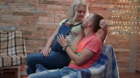 Le jeune couple de HD est dans le studio, l'homme s'assied et son épouse pregant est sur son kness banque de vidéos