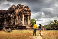 Le jeune couple de silhouette dans l'amour explore l'antique célèbre du temple Angkor Vat de style d'architecture de Khmer Image stock