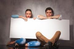 Le jeune couple de sourire est reposant et tenant le conseil vide Photo stock
