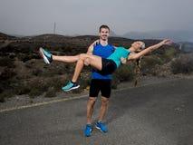Le jeune couple de sport heureux ensemble dehors sur l'homme de paysage de montagne tenant la fille sur le sien fait violence avo Photos libres de droits