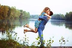 Le jeune couple embrassant et se réjouit au lac Photographie stock libre de droits