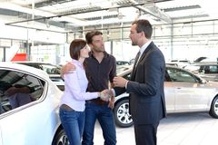 Le jeune couple est conseillé par le vendeur au concessionnaire automobile photographie stock libre de droits