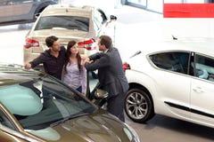 Le jeune couple est conseillé par le vendeur au concessionnaire automobile images stock