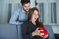 Le jeune couple est heureux avec le cadeau pour Noël Photographie stock libre de droits