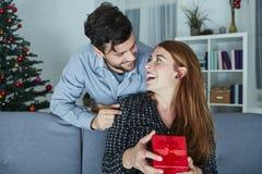 Le jeune couple est heureux avec le cadeau pour Noël Image libre de droits