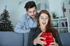Le jeune couple est heureux avec le cadeau pour Noël Photo stock