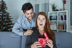 Le jeune couple est heureux avec le cadeau pour Noël Photos stock
