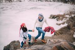 Le jeune couple est marchant et souriant à côté du lac congelé pendant la promenade d'hiver photo libre de droits