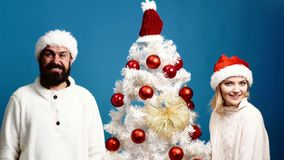 Le jeune couple fait des grimaces tenant l'arbre de Noël proche sur le fond bleu L'homme barbu et la femme blonde se tiennent prê banque de vidéos