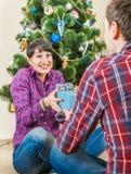 Le jeune couple fait le cadeau de surprise de chrisnmas Photos stock