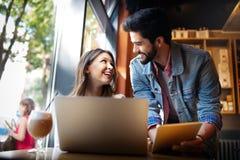 Le jeune couple fonctionne en caf? sur l'ordinateur portable et le sourire photographie stock
