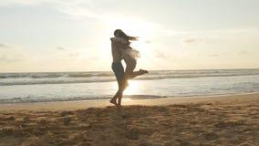 Le jeune couple fonctionne sur la plage, étreinte d'homme et tourne autour sa femme sur le coucher du soleil La fille saute dans  Photographie stock libre de droits