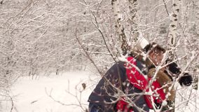 Le jeune couple gai tombe sur la neige dans la forêt banque de vidéos