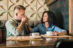 Le jeune couple heureux boit du café et sourit tout en se reposant au café Photo libre de droits