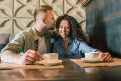 Le jeune couple heureux boit du café et sourit tout en se reposant au café Images libres de droits