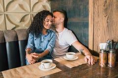 Le jeune couple heureux boit du café et sourit tout en se reposant au café Photos libres de droits