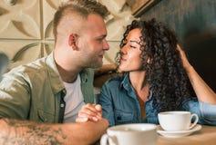 Le jeune couple heureux boit du café et sourit tout en se reposant au café Images stock