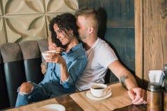 Le jeune couple heureux boit du café et sourit tout en se reposant au café Photographie stock
