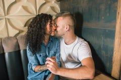 Le jeune couple heureux boit du café et sourit tout en se reposant au café Photo stock
