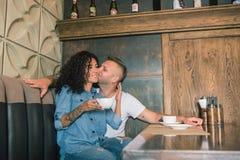 Le jeune couple heureux boit du café et sourit tout en se reposant au café Image libre de droits