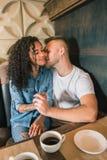 Le jeune couple heureux boit du café et sourit tout en se reposant au café Photos stock