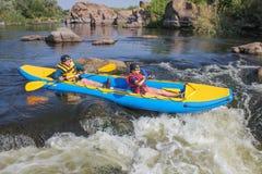 Le jeune couple heureux dans des gilets de vie sourit tout en naviguant un kayak photographie stock libre de droits