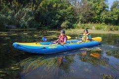 Le jeune couple heureux dans des gilets de vie sourit tout en naviguant un kayak images stock