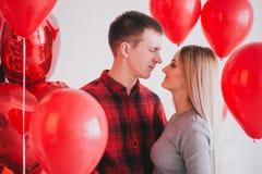 Le jeune couple heureux dans l'amour posant avec le coeur rouge monte en ballon Images libres de droits
