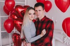 Le jeune couple heureux dans l'amour posant avec le coeur rouge monte en ballon Image libre de droits