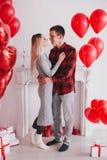 Le jeune couple heureux dans l'amour posant avec le coeur rouge monte en ballon Photographie stock libre de droits