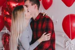 Le jeune couple heureux dans l'amour posant avec le coeur rouge monte en ballon Photographie stock