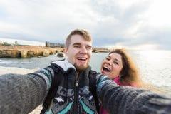 Le jeune couple heureux dans l'amour prend le portrait de selfie sur la plage en Chypre en automne ou hiver Les jolis touristes r Photos stock