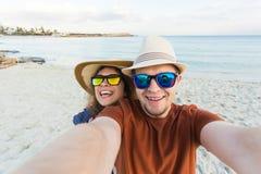 Le jeune couple heureux dans l'amour prend le portrait de selfie sur la plage en Chypre Les jolis touristes font les photos drôle Photographie stock libre de droits